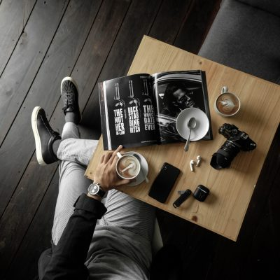 top-view-of-a-table-with-man-holding-a-cup-of-latte-with-a-3098619